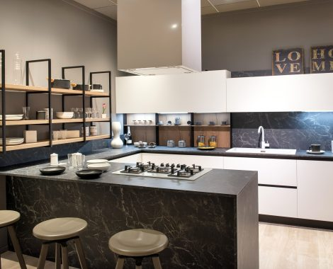 Modern kitchen interior with centre island with bar stools and hob, white cabinets and open shelving